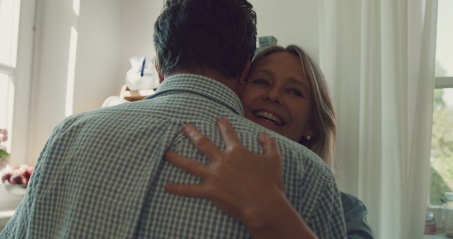 Cinematic shot of lovely happy mature couple is enjoying time together and and having fun dancing to celebrate their timeless love in a kitchen at home. Concept: love, family, marriage, home