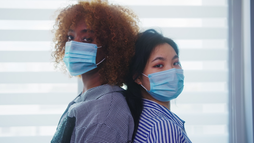 African american and asian women with medical mask standing back to back in front of the window. Multiracial friendshp, bonding during coronavirus. High quality 4k footage Royalty-Free Stock Footage #1062242152