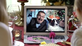 Mature man with a dog and family with a child celebrating Christmas using a video call. People greeting their relatives friends on Christmas eve online. Social distancing, self isolation quarantine