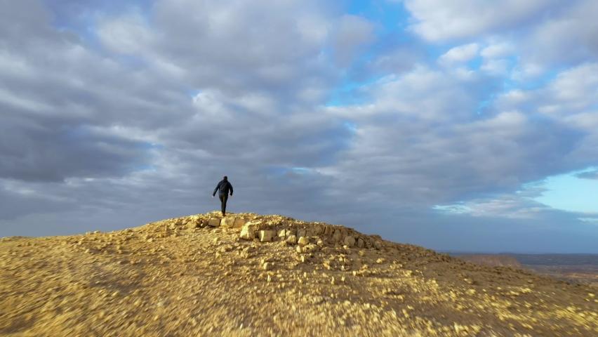 Man Hiking to Mountain Peak Revealing Beautiful Negev Desert Landscape