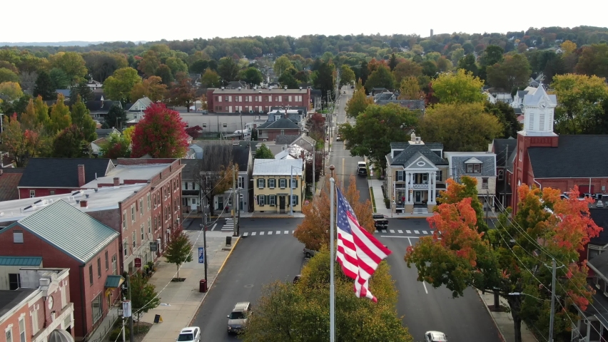Patriotic American flag waves over small town in USA. Descending drone shot. Cinematic aerial. | Shutterstock HD Video #1062245245