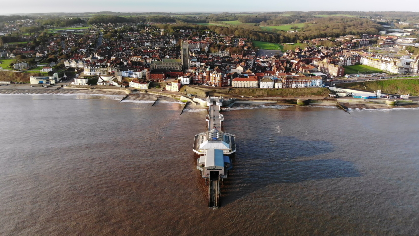 Drone footage from the sea flying over the pier at Cromer, Norfolk towards the town in early morning. | Shutterstock HD Video #1062245314