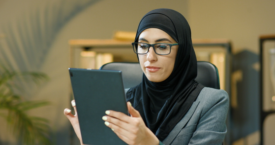 Arabian beautiful woman in black hijab sitting in office, tapping and scrolling on tablet device screen. Muslim bored businesswoman in traditional headscarf browsing on computer Arab female in glasses