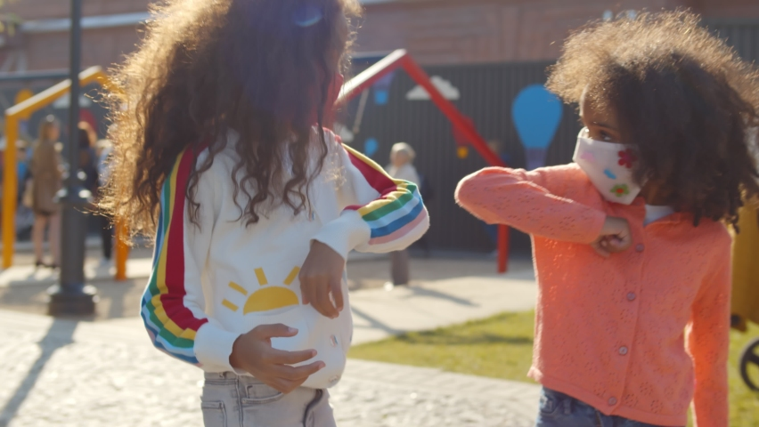 Cute african little girls in safety mask bumping elbow meeting at playground outdoors. Portrait of preschool afro kids greeting with elbow bump playing in park or kindergarten Royalty-Free Stock Footage #1062260545