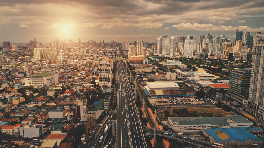 Cityscape at sun light with cross highway, streets, skyscrapers aerial. Bridge traffic road with driving cars at summer sunny day. Philippines capital of Manila town at cinematic drone shot   Shutterstock HD Video #1062272704