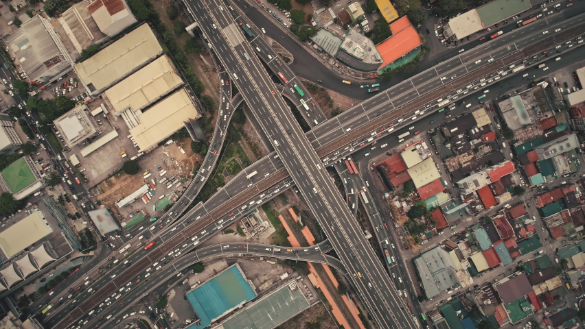 Slow motion top down of cross road traffic with cars, trucks, vehicles in aerial view. Downtown of Manila city with colorful buildings roofs at roadside. Philippines urban lifestyle with local journey | Shutterstock HD Video #1062272755