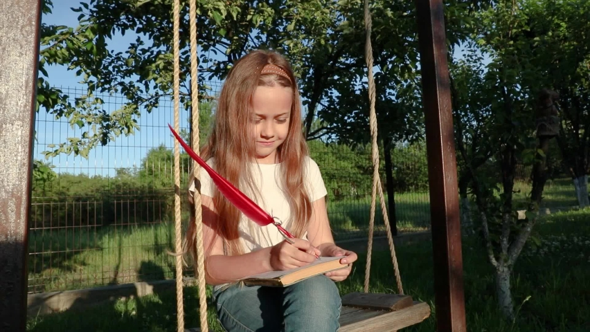 The child writes a letter with a feather pen. a little girl sits on a swing and writes her dreams. the letter in the future