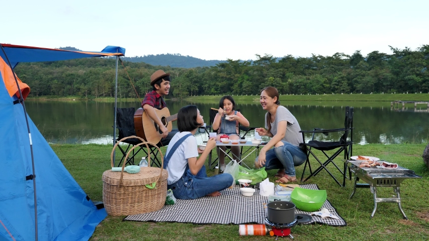 Happy Young Asian Family Sitting Together At Lake Side Camping. Family Relationship Activity.