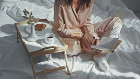 cropped view of woman drinking coffee and reading book in bed