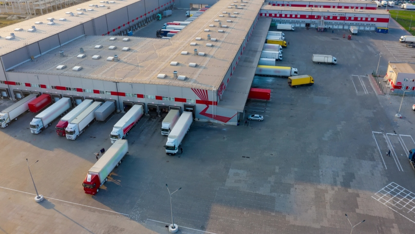 Aerial hyper lapse (motion time lapse) of the logistics park with a warehouse - loading hub. Semi-trucks with freight trailers standing at the ramps for loading/unloading goods at sunset.  Royalty-Free Stock Footage #1062288103