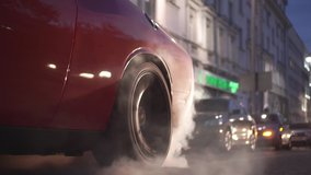 Car burns rubber off its tires in preparation for the race. Footage. Slow motion video of sport vehicles right back wheel the tire burns against the asphalt with smoke