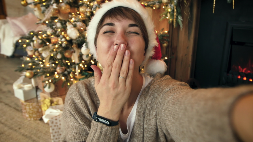 Christmas Selfie Video call during the Pandemic. Young woman calls her parents via video conference call, saying hello and wishing merry christmas Royalty-Free Stock Footage #1062293956
