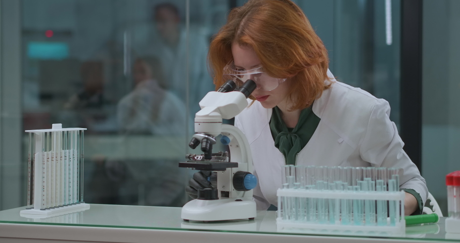 cellular immunology research in scientist laboratory, woman expert is exploring analysis and medicaments in microscope Royalty-Free Stock Footage #1062295798