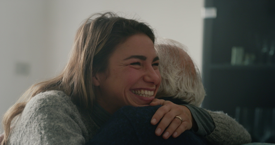 Cinematic shot of senior gray hair grandfather and granddaughter are having fun together and hugging with affection while sitting on sofa at home. Concept: life, grandparents, generation, love, care. Royalty-Free Stock Footage #1062307753