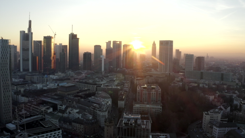 AERIAL: View of Frankfurt am Main, Germany Skyline with sunflair between skyscrapers in Beautiful Sunset Sunlight in Winter Haze | Shutterstock HD Video #1062324829