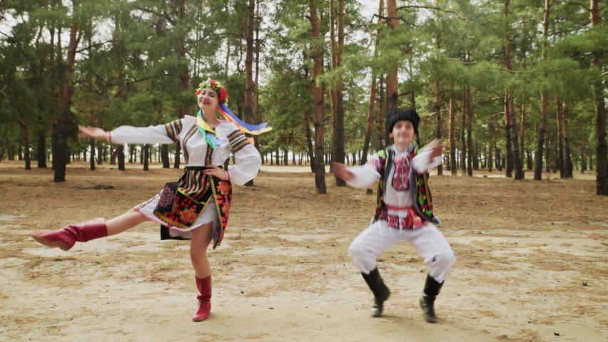 Young woman and man in traditional costumes are dancing Ukrainian national dance Royalty-Free Stock Footage #1062327133