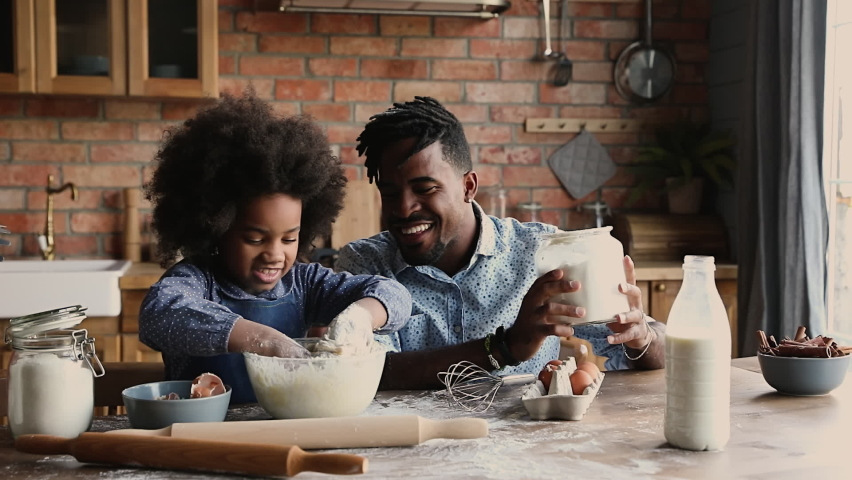 African dad with dreadlocks pour flour while curly haired daughter knead dough in bowl, family prepare surprise sit at dining table in kitchen. Spend time together develop kid, pleasant chores concept