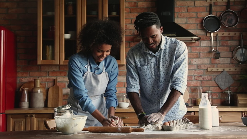 Happy young family African wife and husband standing in cozy kitchen kneading dough cooking together prepare pastries for holiday dinner, celebrate event, enjoy romantic date and communication at home
