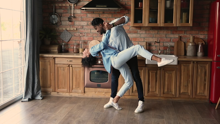 Full length view young African stylish 35s couple, active boyfriend girlfriend in love dancing tango perform passionate and sensual movements in home kitchen. New house, relocation celebration concept #1062340939