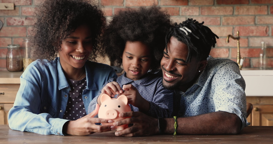 African family with little daughter sit at table in kitchen, preschool 6s girl counts, puts coins in piggy bank, parents teaches child save money, think about future, manage personal savings concept Royalty-Free Stock Footage #1062341029