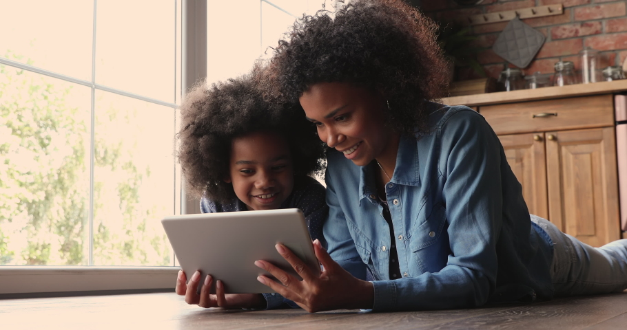 African mother cute little preschool daughter lying on floor at home play on wireless tablet device. Smiling mom small kid girl look at pad screen have fun together use modern electronic tech concept Royalty-Free Stock Footage #1062341041