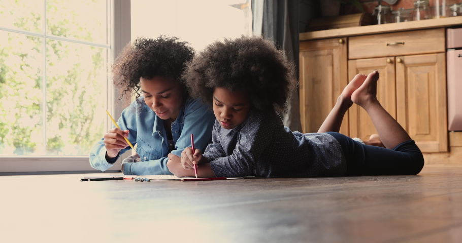 African family spend time at modern home, mother and little 6s daughter chatting while lying on warm wooden kitchen floor draw pictures in sketchbook enjoy hobby and talk. Pastime and leisure concept