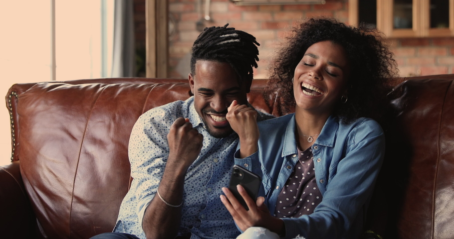African sport fan couple sit on couch at home watching game match on-line in streaming on smart phone celebrating victory. Happy supporters cheering and exulting after winning on internet bet concept Royalty-Free Stock Footage #1062342772