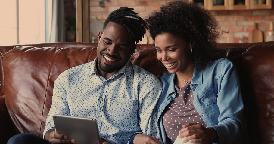 African 30s handsome boyfriend and pretty girlfriend relaxing sit on couch holding tablet, family buy goods for home use e-store on-line e-commerce retail services. Modern tech, new app usage concept Royalty-Free Stock Footage #1062342784