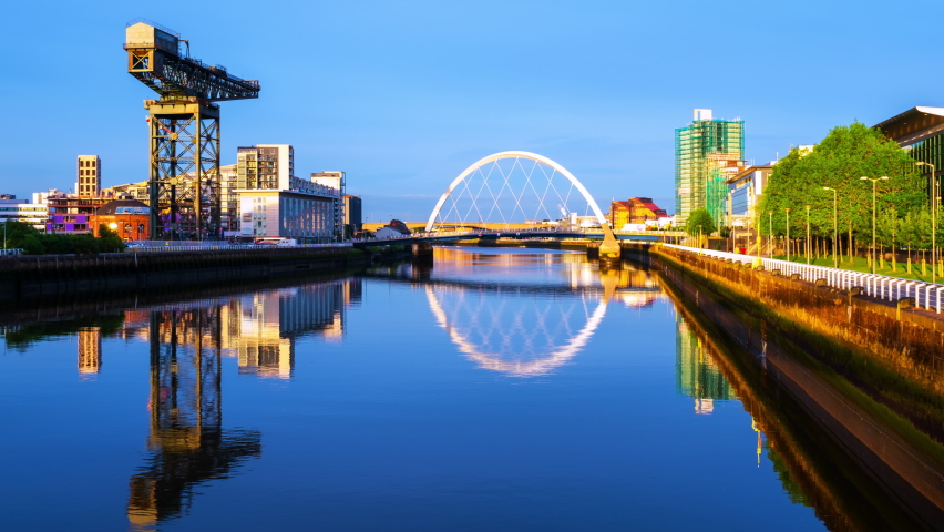 Glasgow, Scotland. View of Glasgow, UK landmarks - Finnieston Crane and Squinty bridge at sunset. Time-lapse with colorful twilight sky