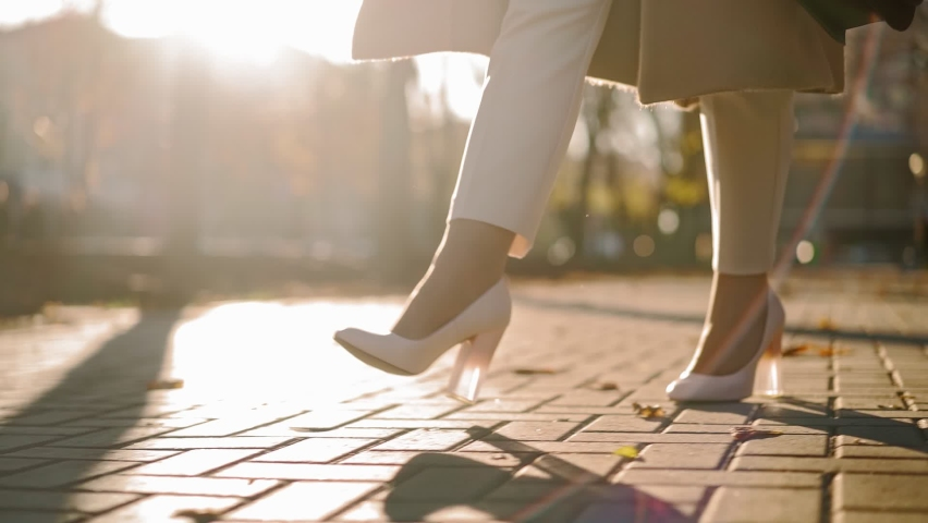 Unrecognizable Beautiful Business Woman Legs in high heels walks through city park to work in the office in autumn in sunset light. Close-up. Slow motion. High quality FullHD footage