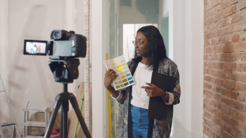 African woman designer choosing paint color for house and recording video for blog. Afro-american decorator blogger filming video on camera having internet blog about renovation Royalty-Free Stock Footage #1062362611