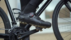 the cyclist wearing special shoes takes off his sneakers and contact pedals
