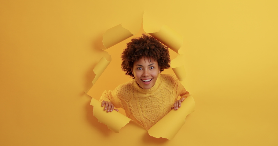 Curious wondered dark skinned woman appears in torn hole has amazed face expression smiles broadly reacts on awesome relevation wears casual jumper poses over yellow background. Wow how great Royalty-Free Stock Footage #1062371692