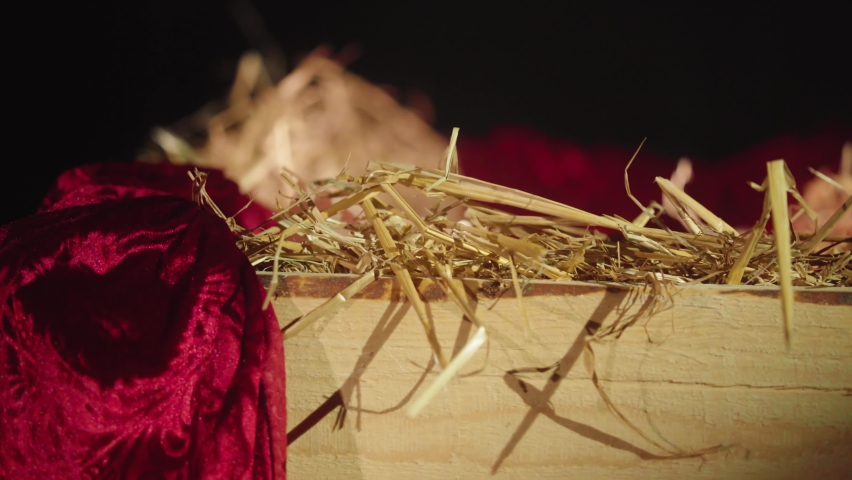 A golden holy decorated Christmas manger which is filled with hay and a red curtain. X-Mas Close Up focus shift shot.