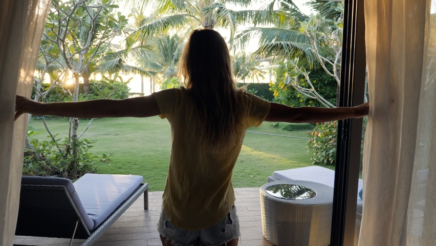 Young woman walking towards room window opens curtains and walks into the garden. Beach bungalow, woman on vacation