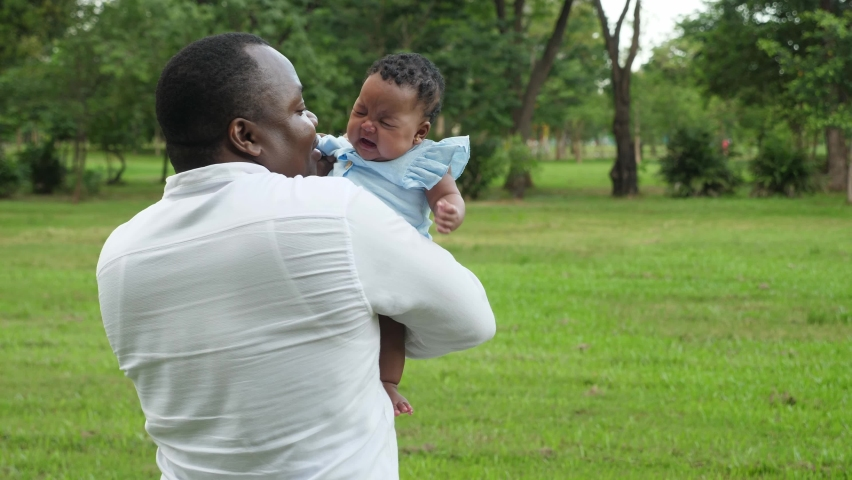 Outdoors, medium shot of happy and kind middle-aged African father cuddle, hold and sing lullaby to calm his crying newborn female colic child at the park