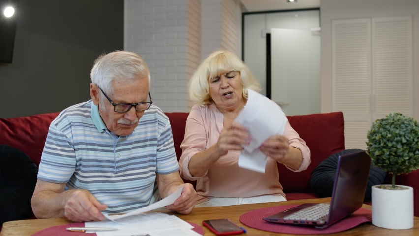 Stressed senior couple discuss unpaid bank debt holding bills, doing paperwork, planning budget, discuss finances calculate mortgage payments at home. Worried elderly grandmother throws paper bills