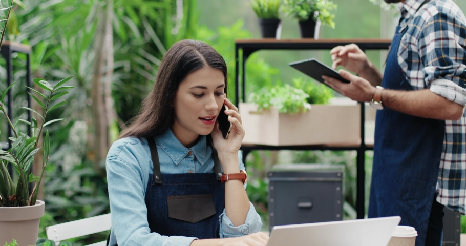 Beautiful busy woman entrepreneur in apron sitting in own floral store and talking on smartphone with client. Caucasian male florist typing on tablet while boss speaking on cellphone. Flower shop