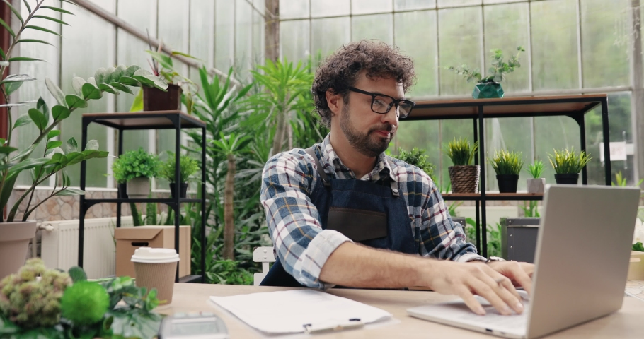 Portrait of Caucasian man entrepreneur in glasses sitting in own flower shop, typing on laptop and writing down in planner. Young male employee in floral store working on computer. Florist concept Royalty-Free Stock Footage #1062400078