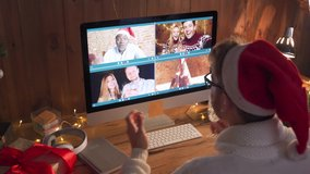 Diverse friends celebrate New Year party on video conference call. Young guy wearing santa hat drinking champagne during virtual Christmas celebration on videocall distance online chat on pc at home.