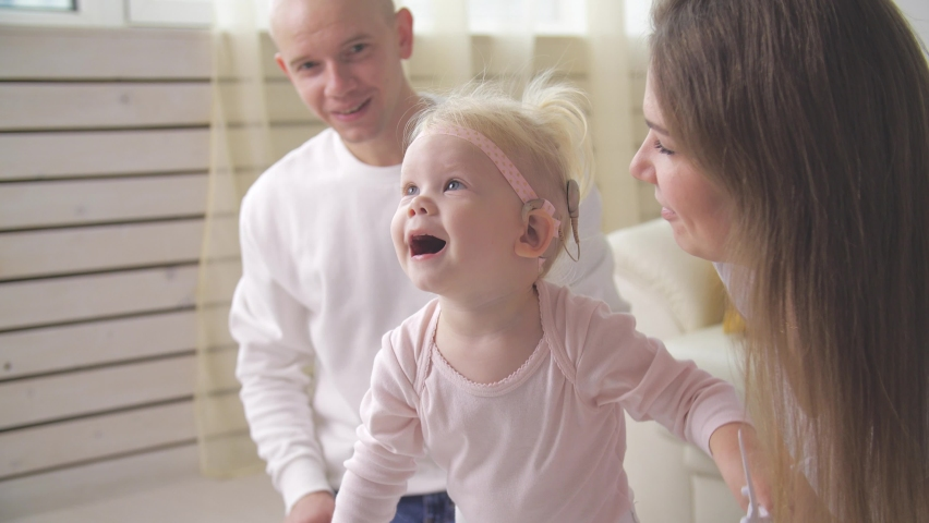Concept of hearing impairment and their treatment. Cute little girl with a Cochlear implant | Shutterstock HD Video #1062401356