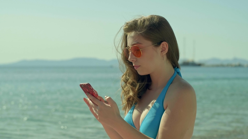 Young woman in bikini using smart phone on the beach. Wearing bikini on vacation. Cellphone addiction on vacation.