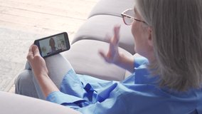 Over shoulder view of older elderly woman patient meeting african virtual doctor using mobile phone at home. Online telemedicine visit. Seniors ehealth, telehealth medical video call consultation.