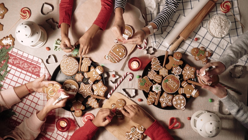 Family is decorating a traditional gingerbread. Xmas flat lay video. Christmas and New Year holidays mood. Group of people glaze a cookie. Top view of home table | Shutterstock HD Video #1062406300