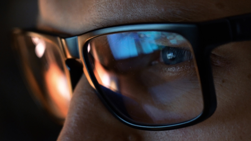 Close up view of focused businessman wears computer glasses for reducing eye strain blurred vision looking at pc screen with computer reflection using internet, reading, watching, working online late. Royalty-Free Stock Footage #1062406840
