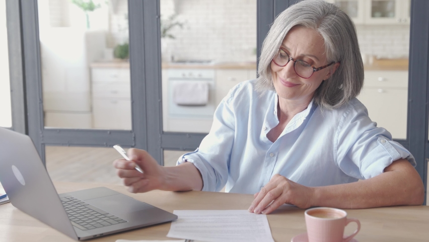 Senior older business woman distance teacher, online coach, lawyer, consultant talking working with documents, making video conference call virtual chat meeting on laptop working from home in office. Royalty-Free Stock Footage #1062406870
