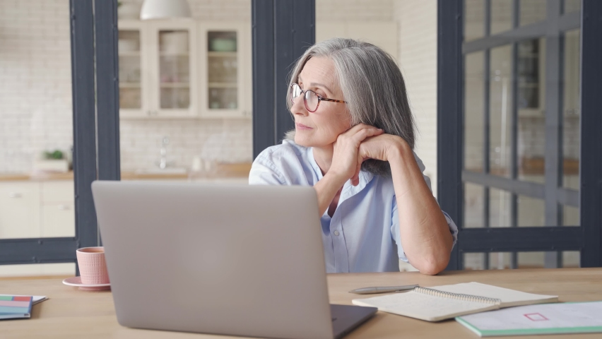 Thoughtful serious doubtful smart senior middle aged old woman looking away thinking of future vision, problem or question, business challenges, feeling doubt, sitting at home office work desk. Royalty-Free Stock Footage #1062406876