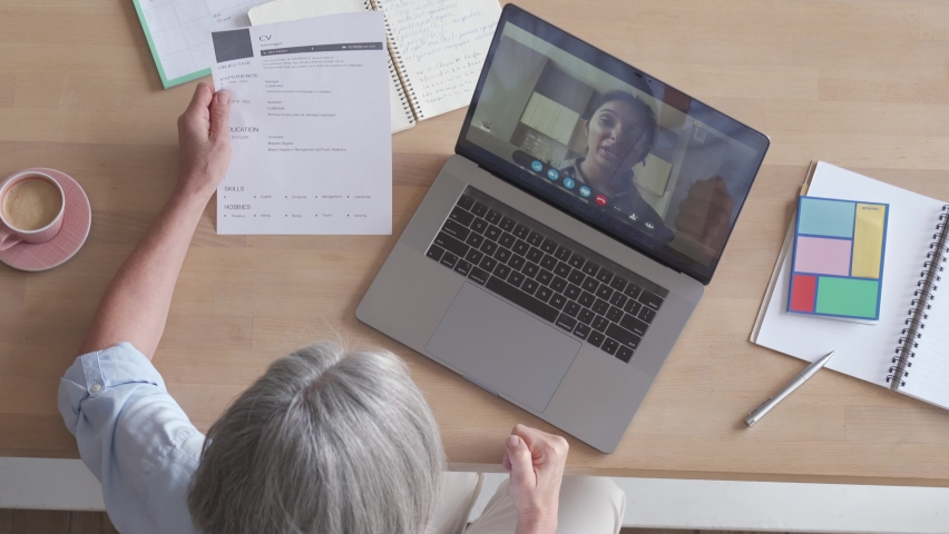 Senior female recruiter talking during social distance job interview by video call. Elderly hr hiring female applicant communicating in conference virtual chat videocall meeting on laptop, top view. Royalty-Free Stock Footage #1062406879