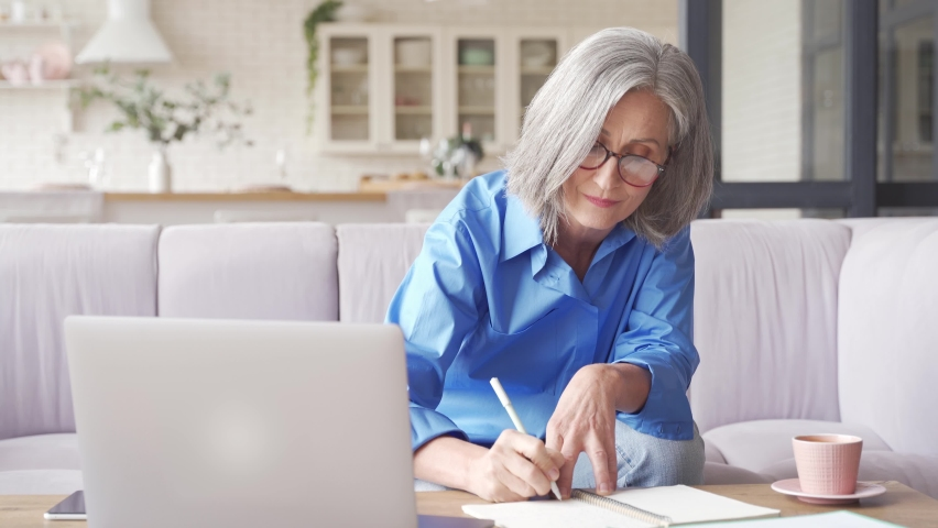 Middle aged senior older woman elearning online concept, watching business training class, live webinar on laptop computer remote working, social distance learning, writing notes from home office. Royalty-Free Stock Footage #1062406882