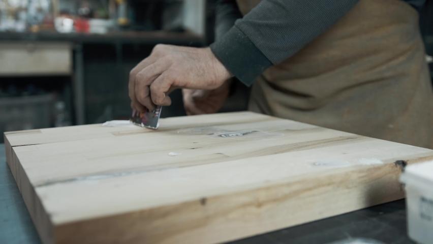 A carpenter applies a putty to a loft-style chair made of wood. | Shutterstock HD Video #1062411694